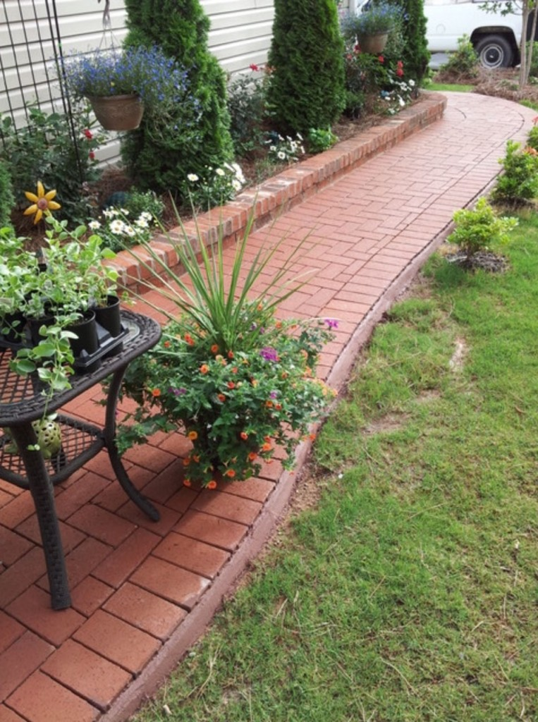 Patio and brick planter by Charlotte Pavers and Stone.